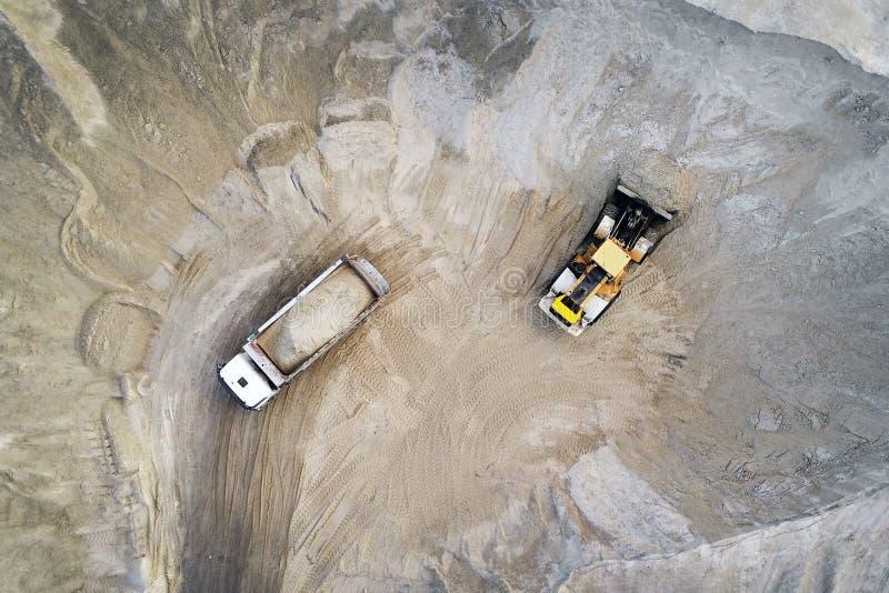 Areia de carregamento do carregador pesado grande da roda no caminhão basculante no poço de areia Conceito pesado da maquinaria i imagem de stock royalty free