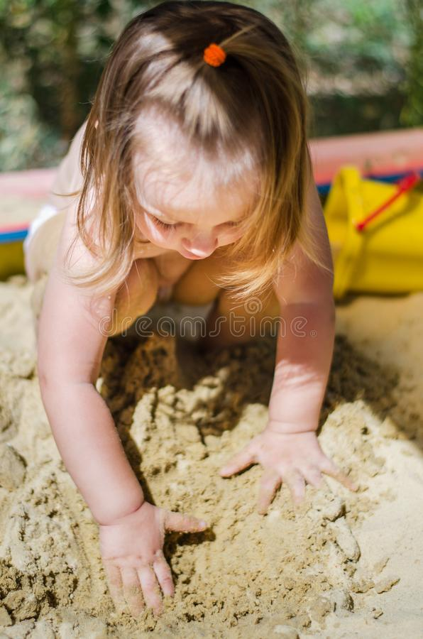 Areia de escavação da menina na caixa de areia foto de stock