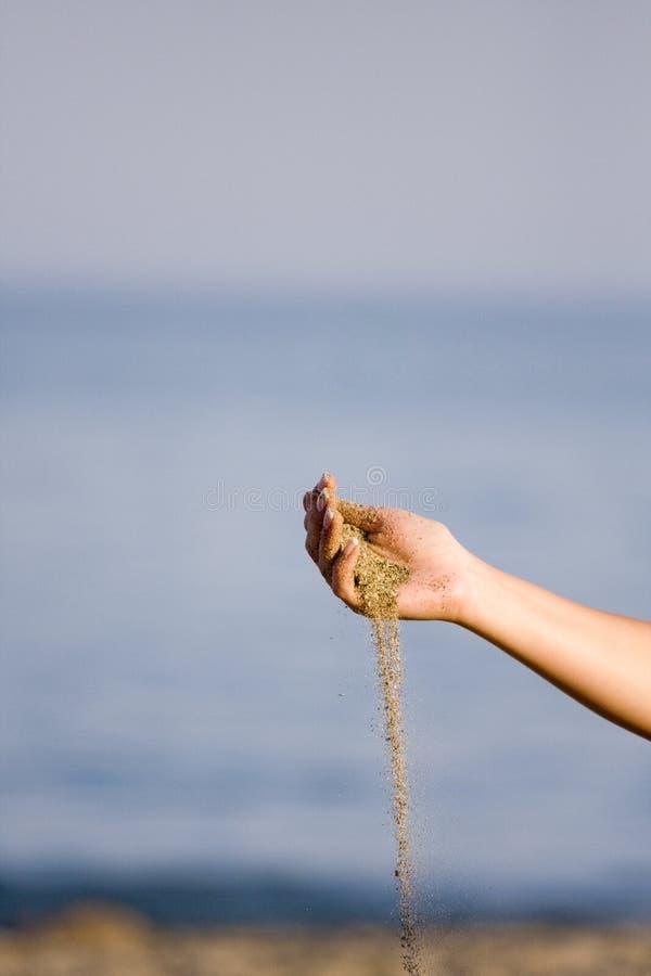Areia deixando cair da mão da mulher imagens de stock royalty free