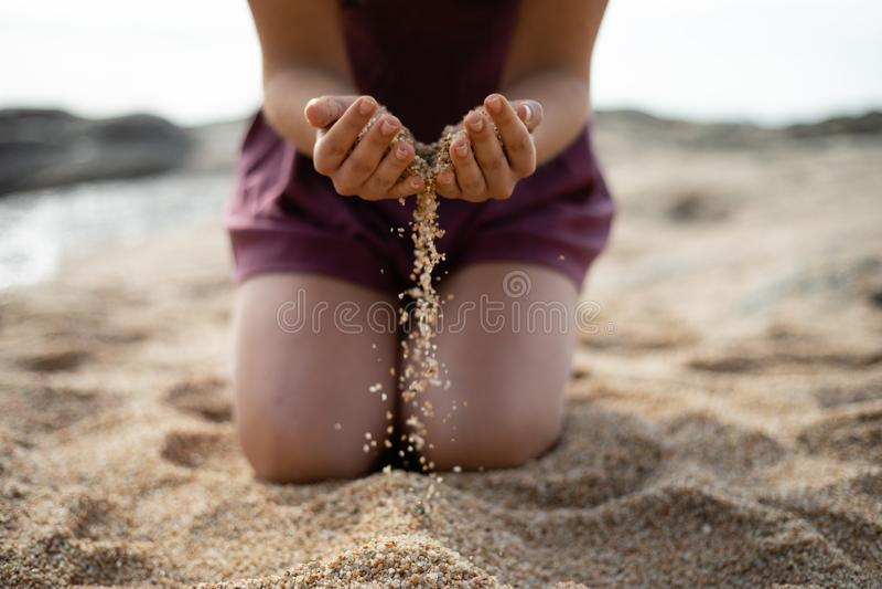 Areia deixando cair da menina da genuflexão de ambas as mãos fotografia de stock royalty free