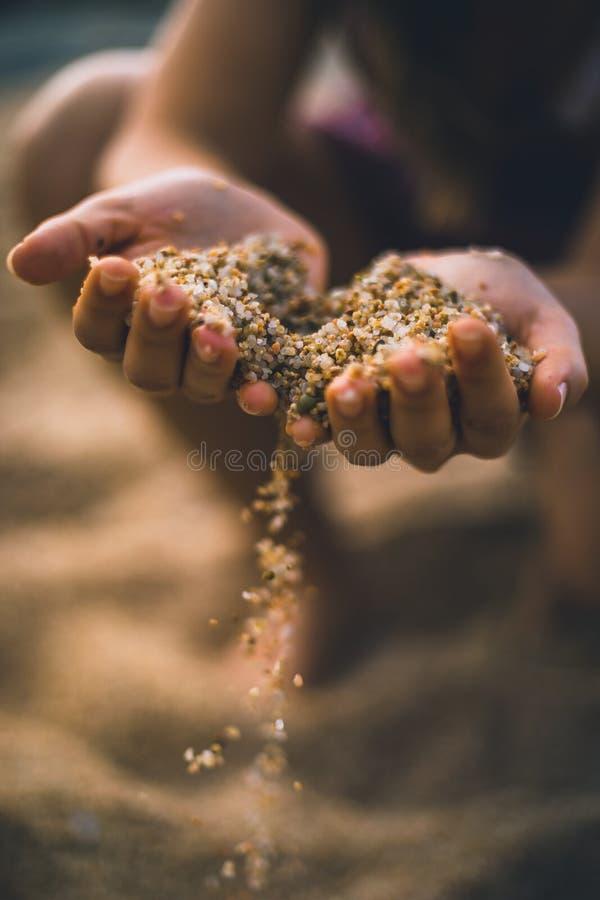 Areia deixando cair de ambas as mãos da mulher fotos de stock royalty free
