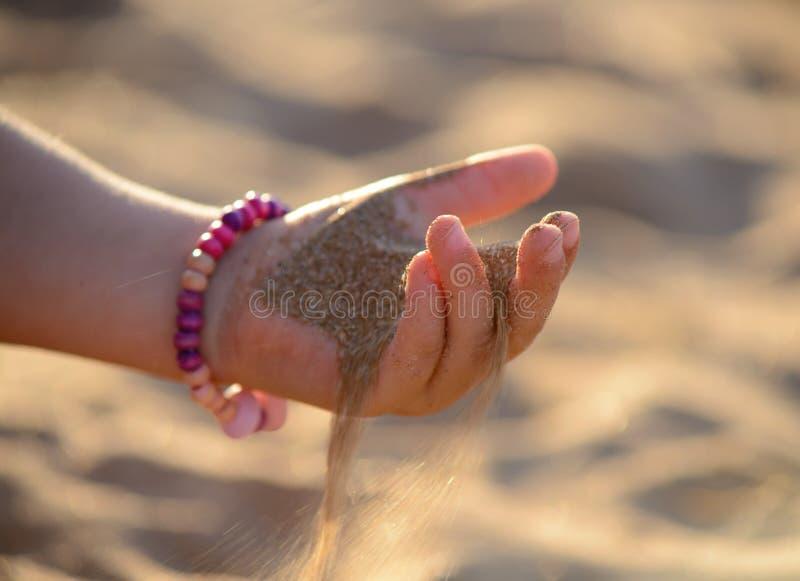 A areia derrama fora da mão da criança fotografia de stock royalty free