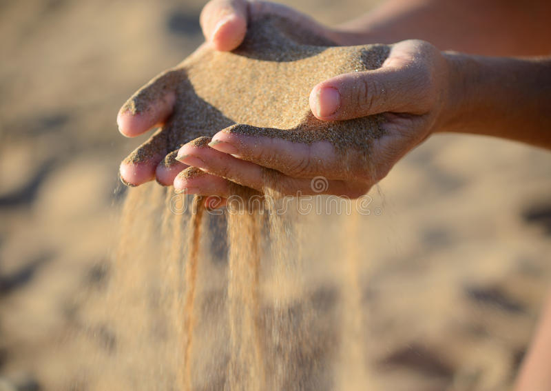 A areia derrama fora das mãos imagens de stock