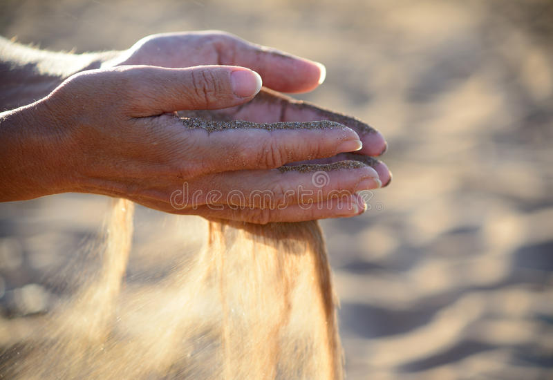 A areia derrama fora das mãos imagens de stock royalty free