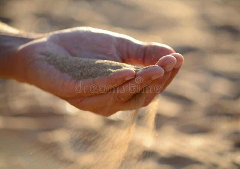 A areia derrama fora das mãos fotos de stock