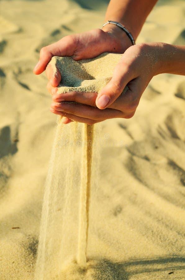 A areia derrama fora das mãos fêmeas fotografia de stock