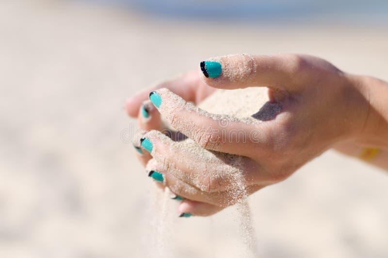 A areia derrama fora das mãos fêmeas imagem de stock royalty free