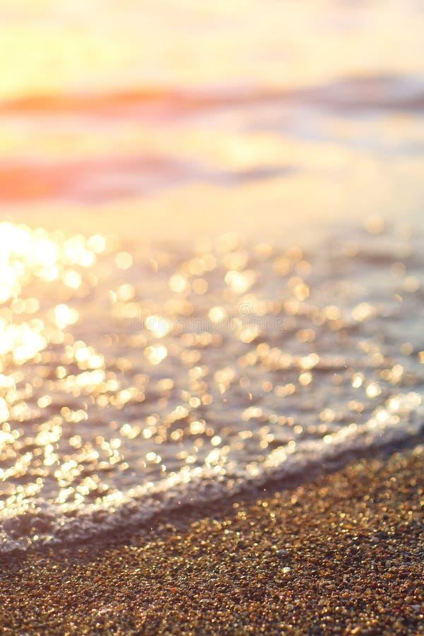 Areia molhada do mar na praia contra o por do sol dourado bonito do fundo Feche acima da areia do mar no oceano da costa durante  imagens de stock