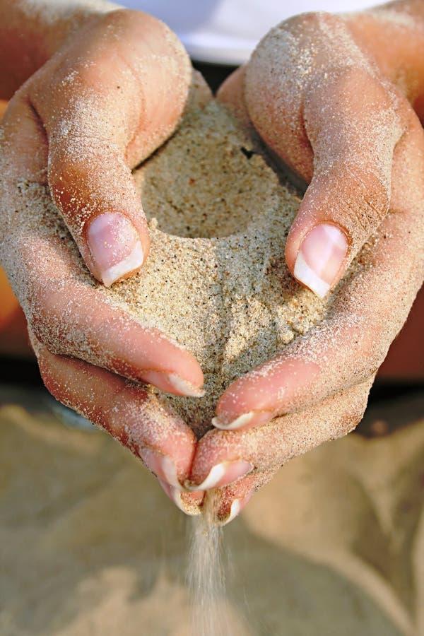 Areia nas mãos bonitas fotografia de stock