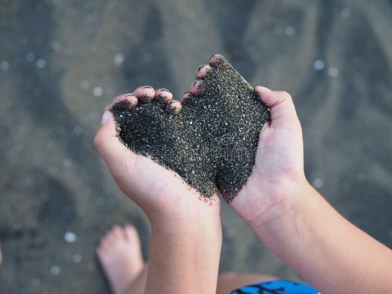 Areia preta nas mãos das crianças sob a forma de um coração foto de stock