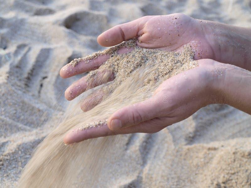 Areia que cai das mãos imagem de stock