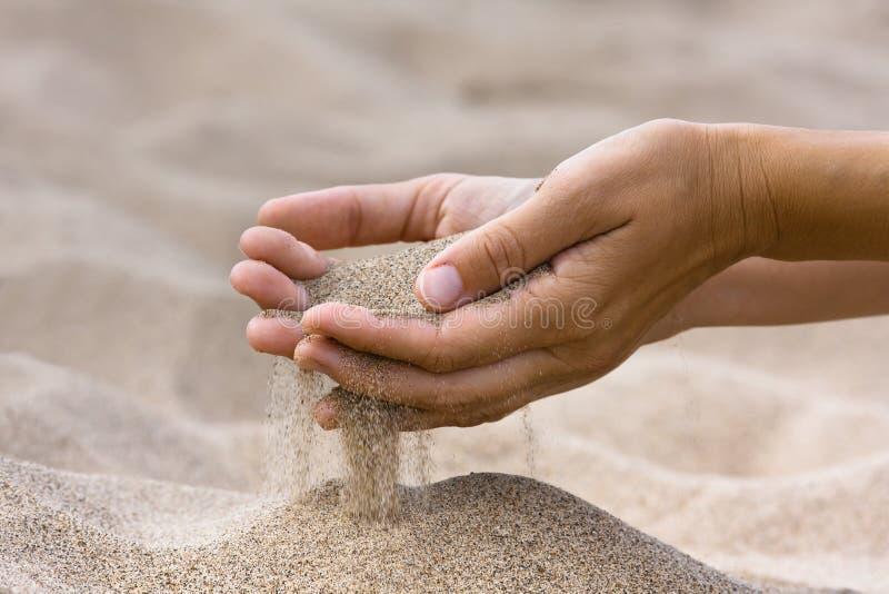 Areia que corre através das mãos da mulher imagem de stock