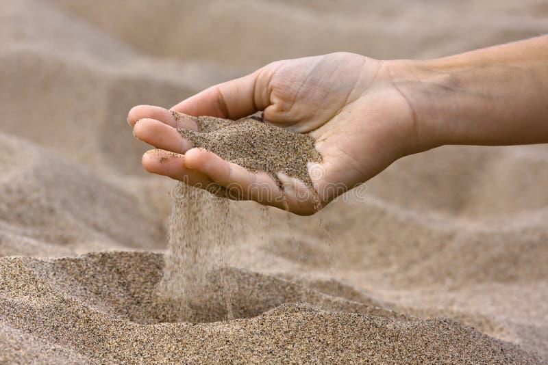 Areia que corre através dos dedos foto de stock