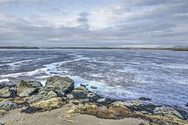 Areia, rochas, mudflats e céu fotografia de stock royalty free