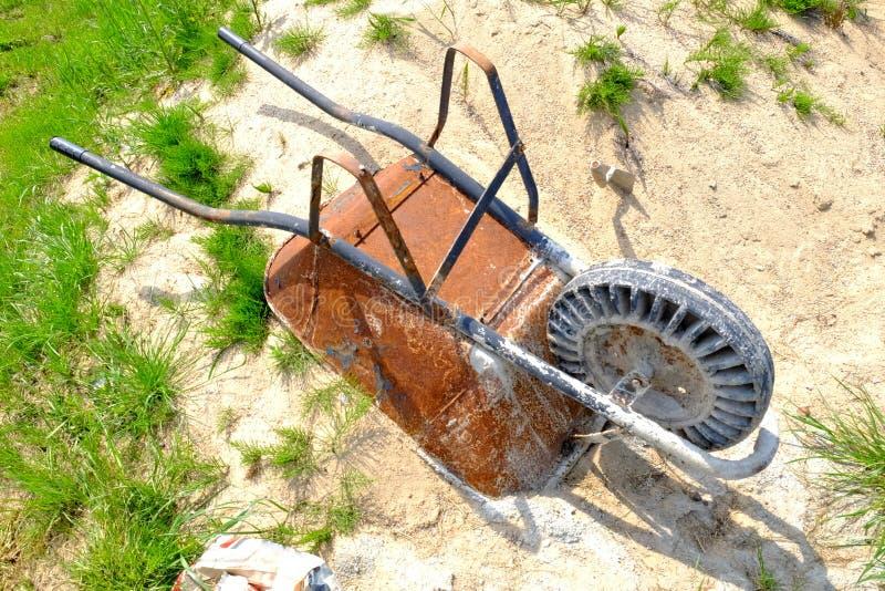 Areia só de Rusty Wheelbarrow Sitting On The com grama pequena ao redor fotos de stock