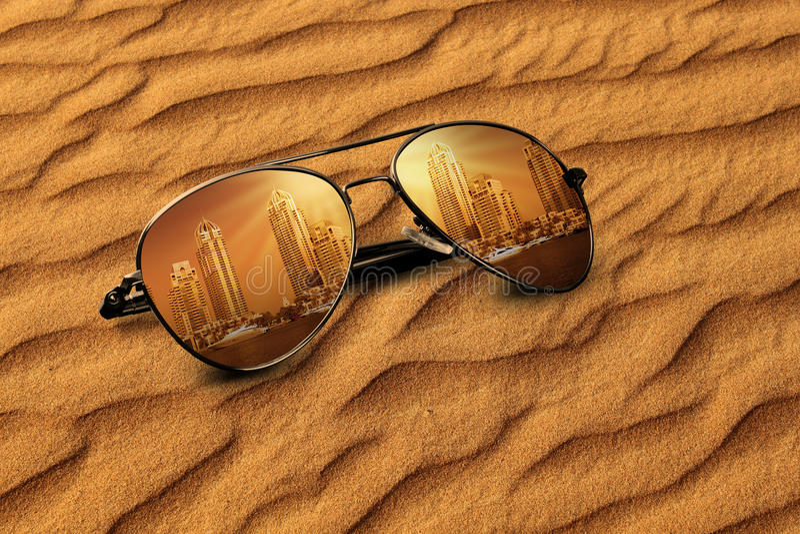 Areia velha de Dubai do conceito & reflexões novas de Dubai em óculos de sol imagem de stock royalty free