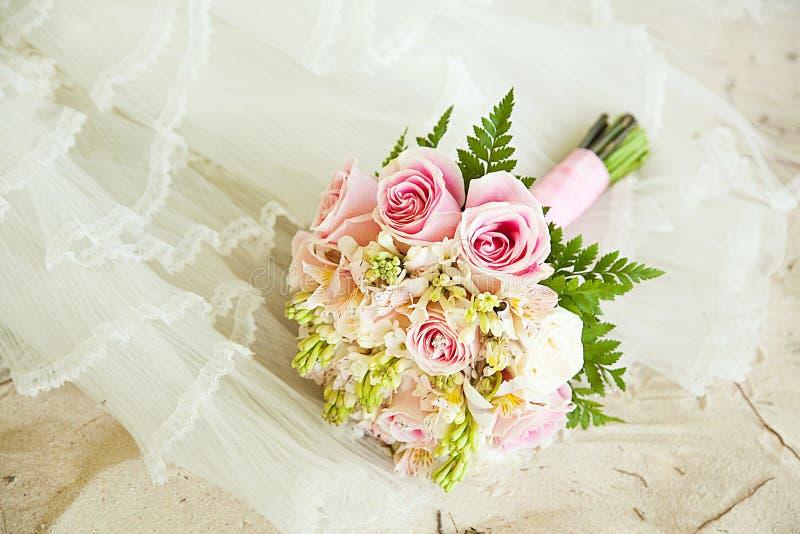 Areia, vestido de casamento e ramalhete brancos fotos de stock