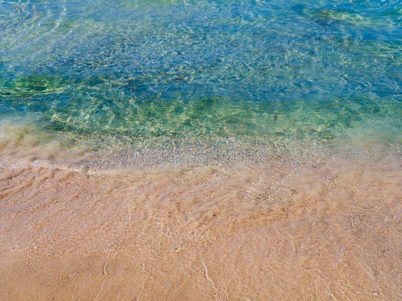 Areias alaranjadas e água azul claro - praia vazia na Creta, Grécia imagem de stock