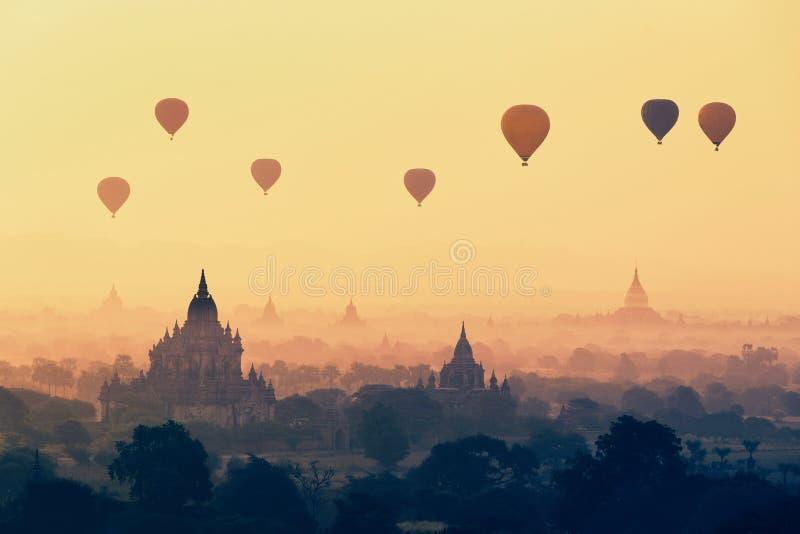 Areje os balões quentes que flutuam no pagode superior em Bagan, Myanmar imagem de stock