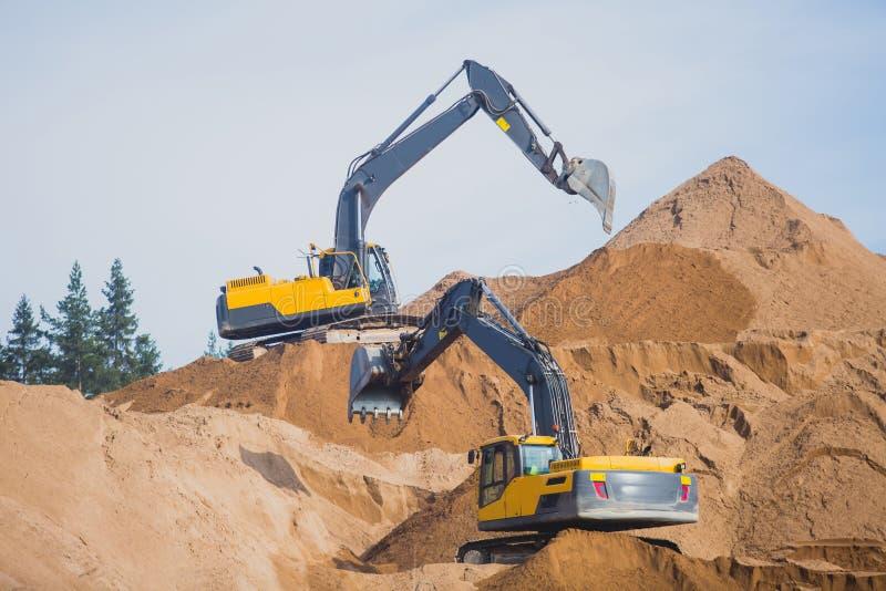 Arena de excavación pesada amarilla del excavador y de la niveladora y trabajo durante obras viales, descargando el metal de la a imágenes de archivo libres de regalías