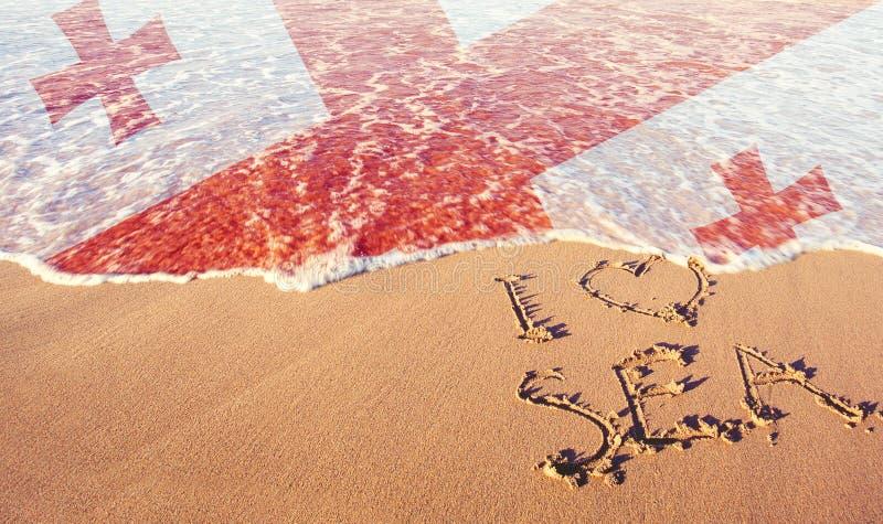 Arena de la playa, mar y bandera Georgia Amo el concepto de Georgia fotografía de archivo libre de regalías