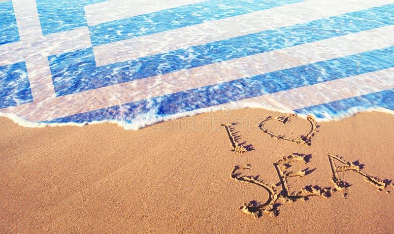 Arena de la playa, mar y bandera Grecia Amo el concepto de Grecia foto de archivo