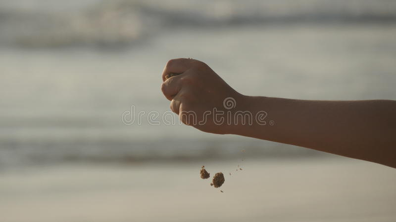 Arena de mar de colada de la mano femenina a través de sus fingeres en la puesta del sol contra un fondo del océano Brazo de la m fotos de archivo