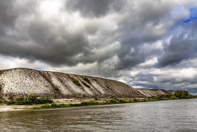 Arena del cuarzo en la orilla del río, contra el contexto de las nubes de lluvia foto de archivo