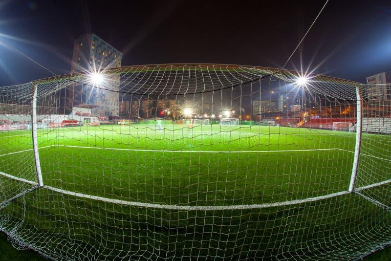 Arena del fútbol en proyectores brillantes iluminados noche fotografía de archivo