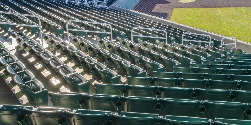 Arena deportiva con las gradas de sitios vacíos iluminados por el sol fotos de archivo libres de regalías