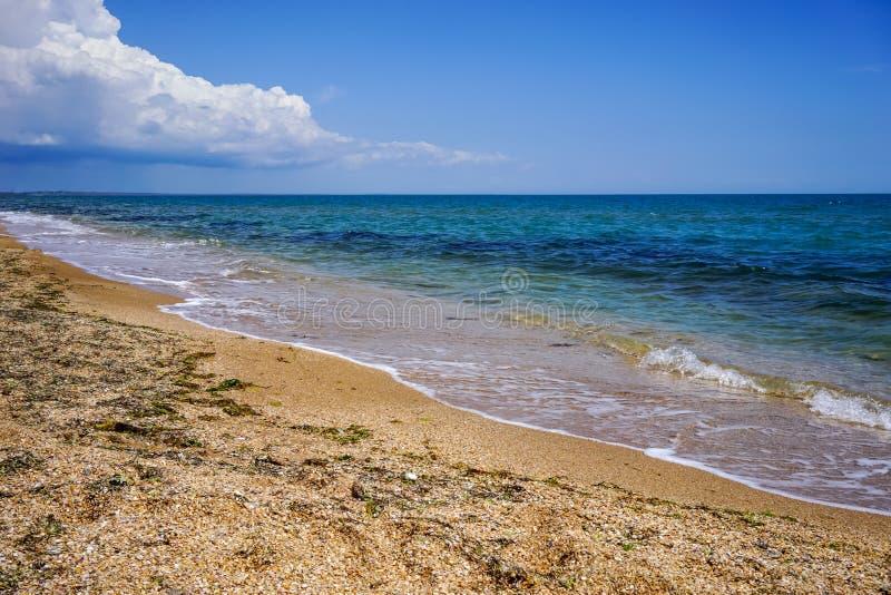 Arena y playa de la cáscara del mar en la Crimea en el fondo del mar azul brillante y del cielo claro fotos de archivo libres de regalías