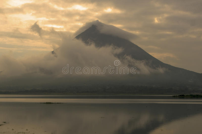 Arenal Volcano During Sunset. The sun spewing its orange light over Arenal volcano during sunset royalty free stock images