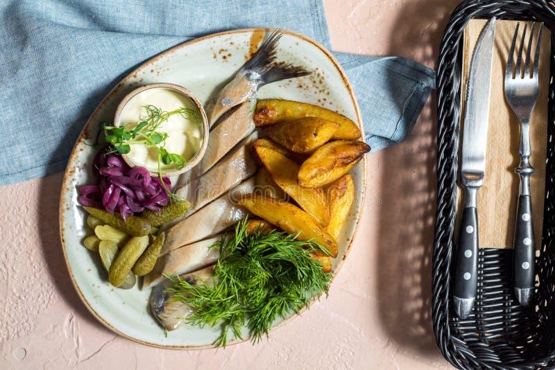 Arenques com as batatas cozidas caseiros, pepino conservado conservado Verdes frescos e alface Prato nacional bielorrusso imagens de stock