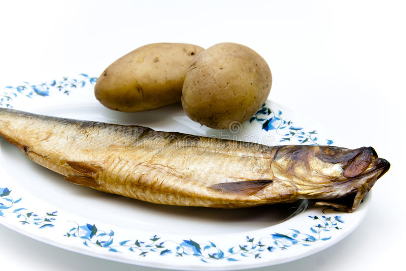 Arenques con las patatas de la peladura en la placa fotos de archivo