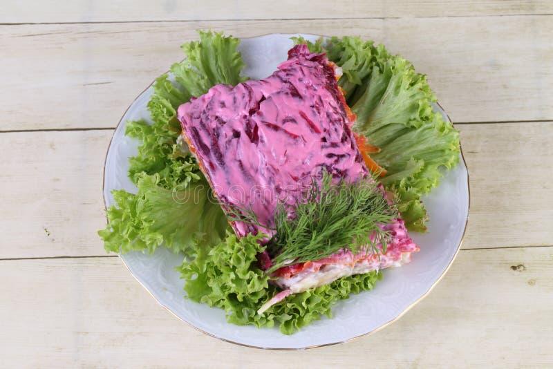 Arenques do ` da salada sob um ` do casaco de pele Salada mergulhada com vegetais e os peixes salgados com molho branco foto de stock