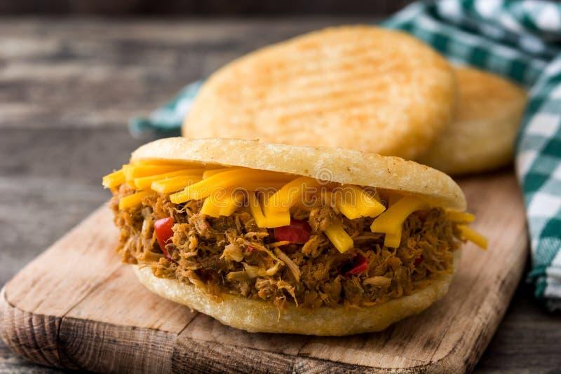 Arepa com carne e queijo shredded no fundo de madeira Alimento típico do venezuelano fotos de stock