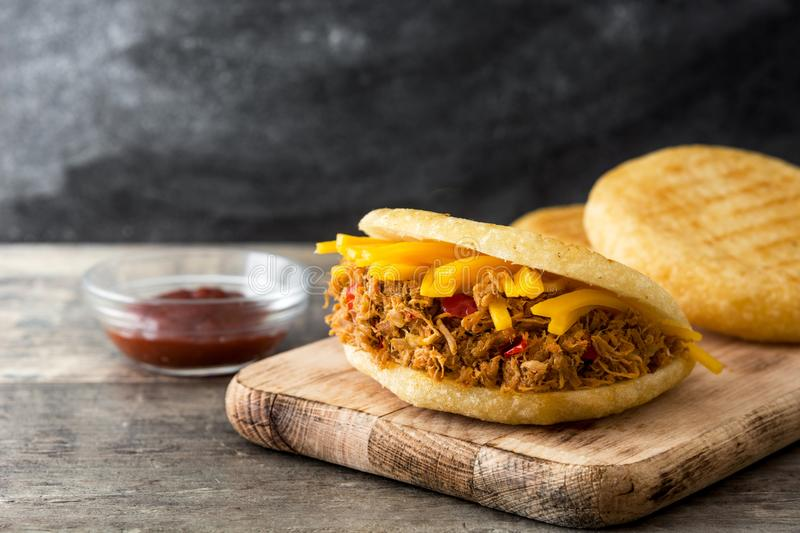 Arepa with shredded beef and cheese on wood. Venezuelan typical food. Arepa with shredded beef and cheese on wooden background. Venezuelan typical food royalty free stock image