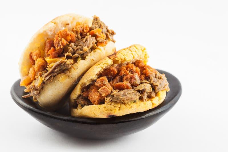Arepas ha riempito di manzo tagliuzzato e la scorza della carne di maiale è servito in un piatto ceramico nero immagini stock