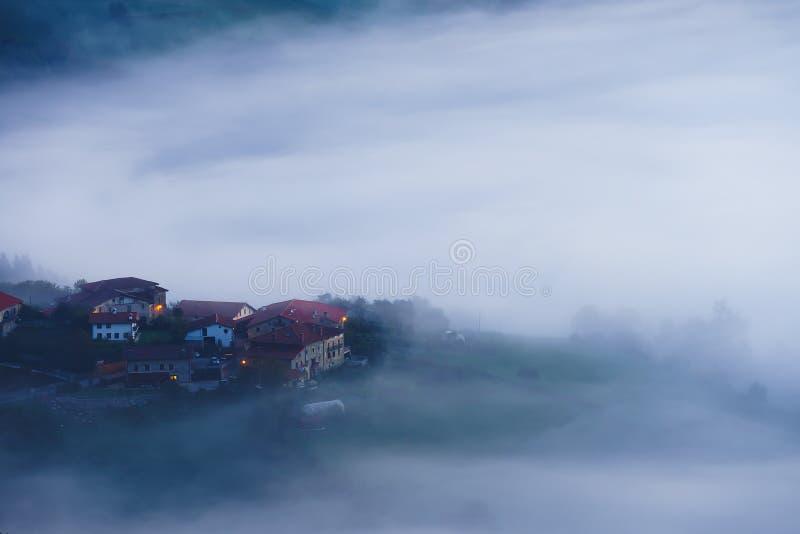 Arexoladorp in Aramaio bij ochtend met overzees van mist stock foto's
