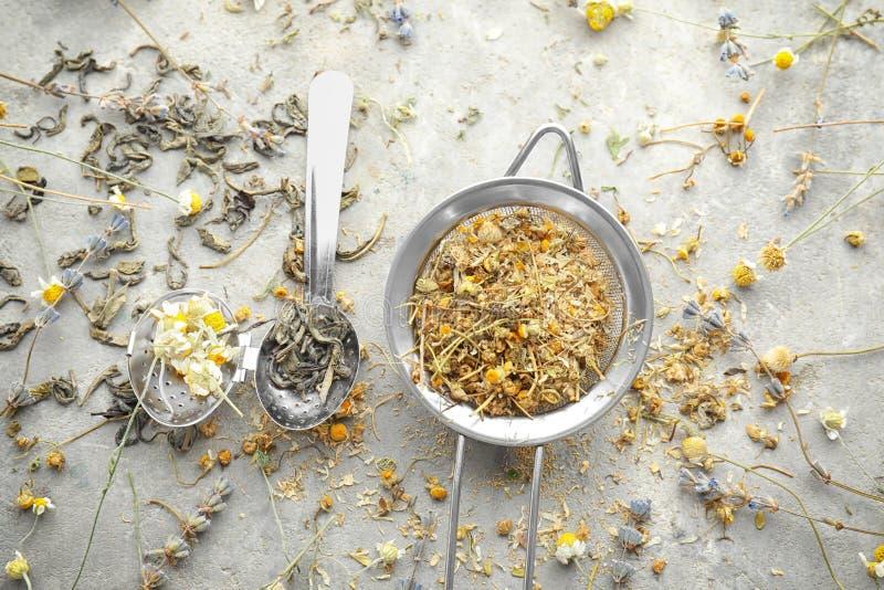 Arfa i durszlak z wysuszonymi herbacianymi liśćmi i chamomile kwitniemy na światło stole zdjęcie stock