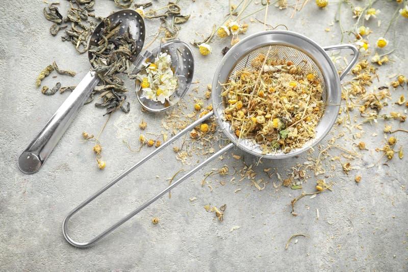 Arfa i durszlak z wysuszonymi herbacianymi liśćmi i chamomile kwitniemy na światło stole fotografia stock