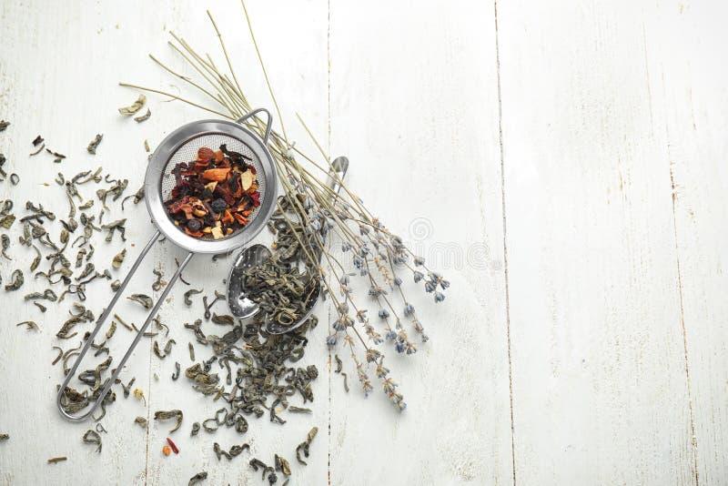 Arfa i durszlak z wysuszonymi herbacianymi liśćmi i lawendą na białym drewnianym stole zdjęcie stock