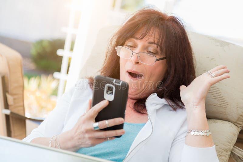 Arfadas envelhecidas meio chocadas da mulher ao usar seu telefone esperto fotografia de stock royalty free