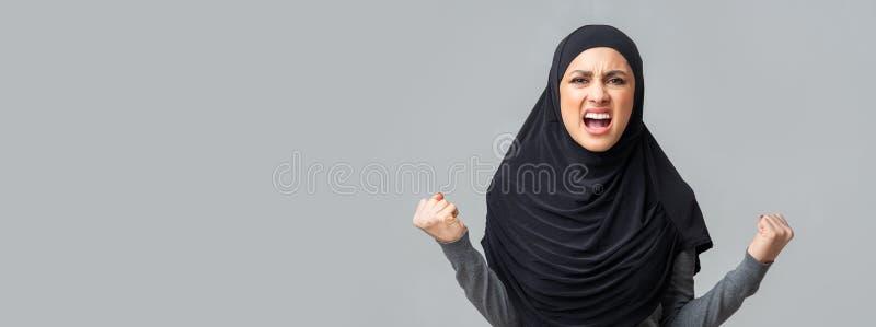 Arg emotionell arabisk flicka som skriker i raseri över grå studions bakgrund arkivfoto