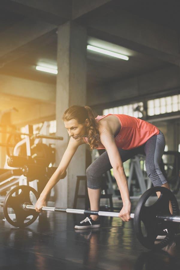 Arg färdig kropp och muskulösa lyftande skivstångvikter i idrottshallen, sportkvinna som gör övningsutbildning royaltyfria bilder