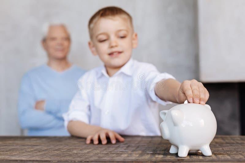 Argent économiquement inspiré de jeune garçon pour un rêve image stock