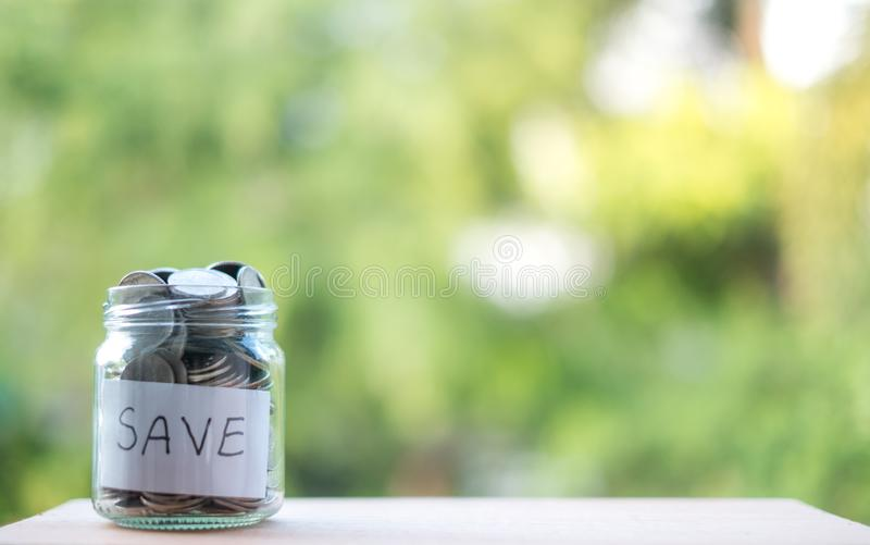 Argent économisant dans la bouteille pour le futur investissement d'argent liquide dedans, avec un fond vert photographie stock libre de droits