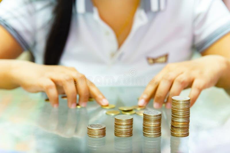 Argent économisant, femme empilant des pièces de monnaie en colonnes croissantes images libres de droits
