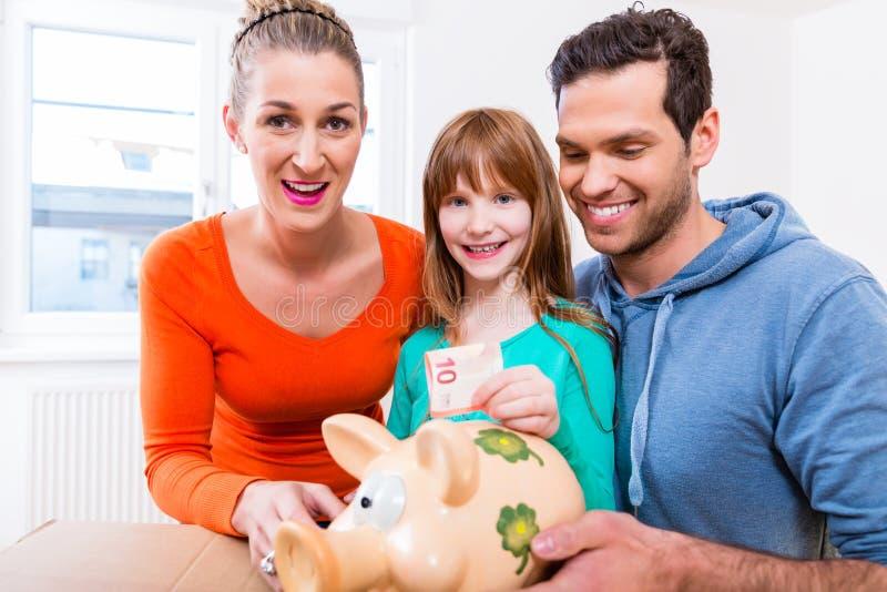 Argent d'économie de famille en déplaçant la maison photographie stock