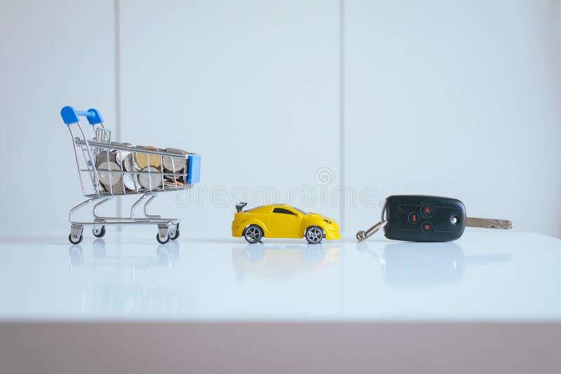 Argent d'économie pour des voitures avec des pièces de monnaie sur le mini chariot de chariot à achats, les finances de voiture e images stock